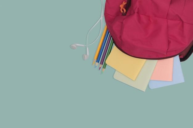 Saco de escola com livro e lápis de cor, volta ao conceito de escola