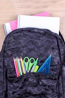 Saco de escola preto com um conjunto de artigos de papelaria para o aluno e com o caderno branco nele.