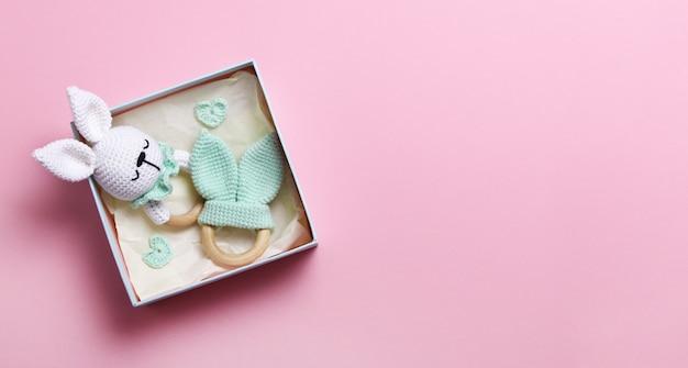 Saco de feijão e mordedores de brinquedos de madeira ecológicos de bebê em caixa com fundo rosa com espaço de cópia