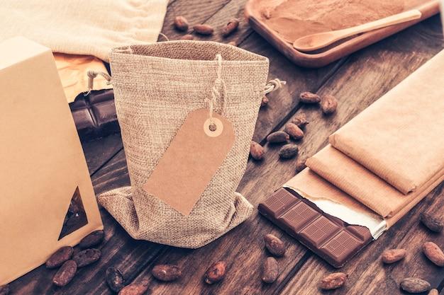 Saco de grãos de cacau com pilha de barras de chocolate na mesa de madeira