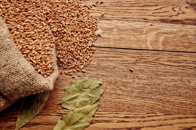 Saco de grãos na mesa de madeira, agricultura, ingrediente alimentar saudável