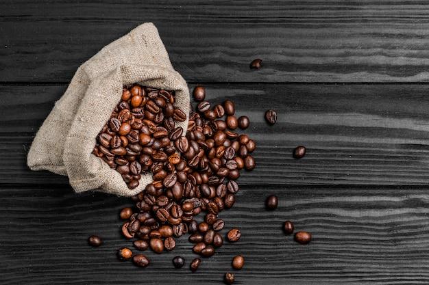 Saco de juta cheio de grãos de café torrados e espalhados sobre uma mesa de madeira