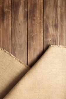 Saco de juta de serapilheira na mesa de fundo de madeira, vista superior