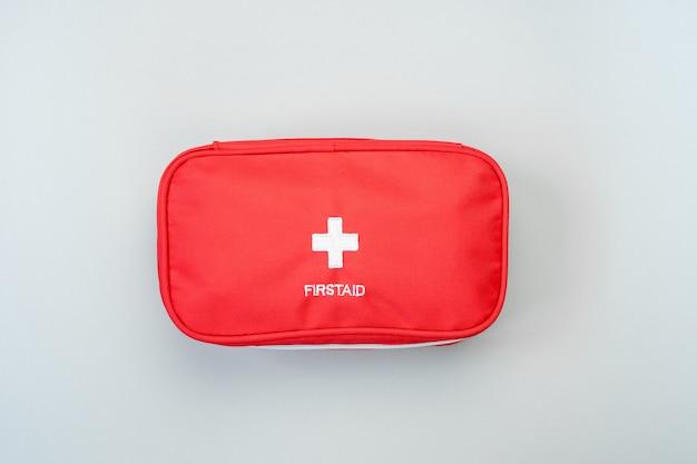 Saco de kit de primeiros socorros vermelho sobre fundo cinza. conceito de tratamento médico de emergência.