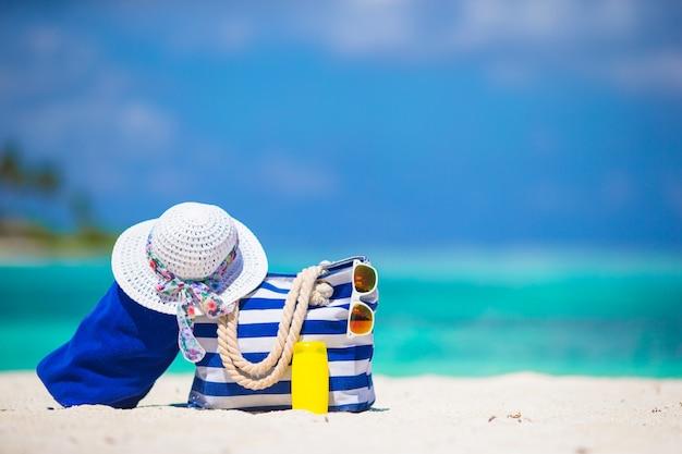 Saco de listra azul e toalha, chapéu de palha branca, óculos de sol, protetor solar garrafa na praia exótica