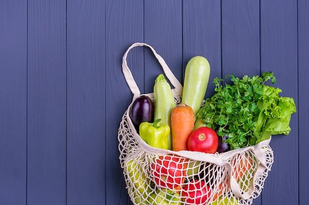 Saco de loja de malha amigável de eco com vegetais verdes orgânicos em madeira cinza escuro.