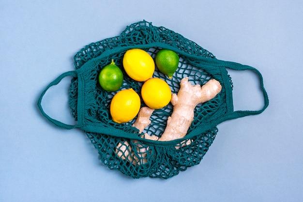 Saco de loja de malha ecológica com limão verde orgânico, limão, gengibre