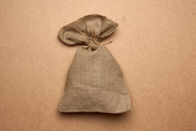 Saco de lona cheia amarrado com corda em um fundo de madeira marrom, vista superior