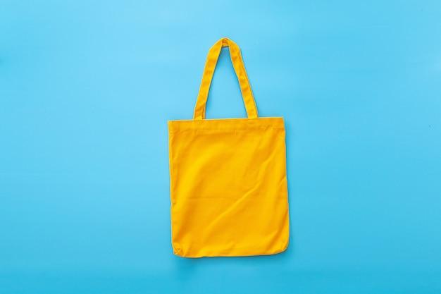 Saco de lona ou saco de pano feito de materiais naturais com fundo azul. idéias para reduzir sacos de plástico.