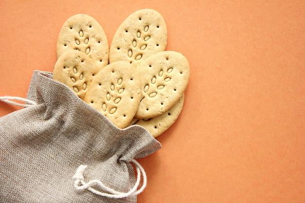 Saco de lona reutilizável e biscoitos multigrãos.