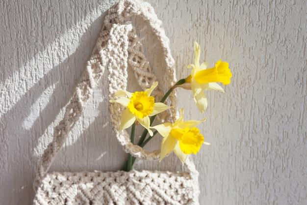Saco de macramê feito à mão na parede clara.