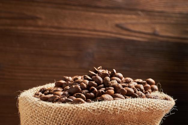 Saco de malha com grãos de café no contexto de um fundo de madeira adorado. copie o espaço.