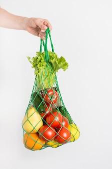 Saco de malha com legumes na mão de uma mulher.