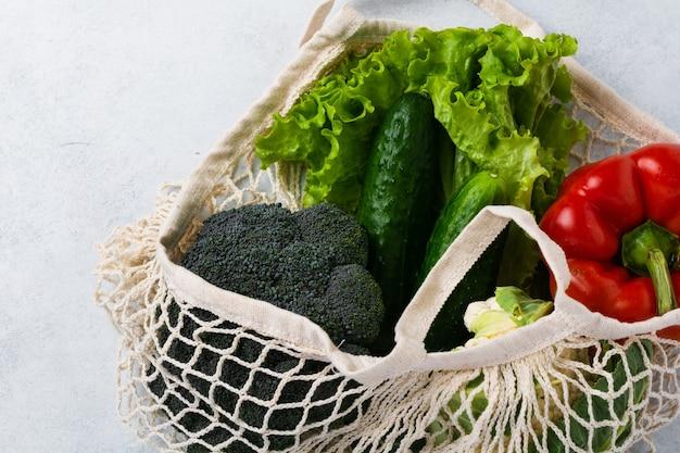 Saco de malha com legumes. zero desperdício e conceito de comida vegana e vegetariana de saúde.