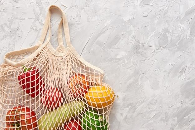 Saco de malha ecológico com frutas e vegetais.