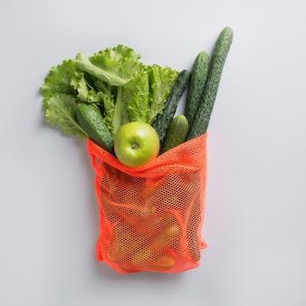 Saco de malha moderna com vegetais verdes. desperdício zero.