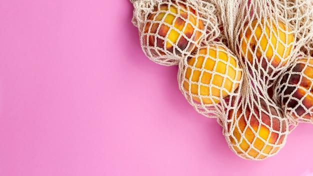 Saco de malha reutilizável com pêssegos