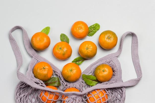 Saco de malha reutilizável com tangerinas. postura plana. copie o espaço