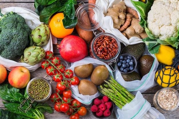 Saco de malha têxtil com produtos, frutas e vegetais. conceito de compras de supermercado sustentável, reciclável, reutilizável e sem resíduos de plástico zero. fundo plano