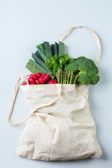 Saco de malha têxtil com produtos, frutas e vegetais. conceito zero desperdício, ecológico, reciclado sem plástico e reutilizável. espaço de cópia, plano de fundo de coral branqueado