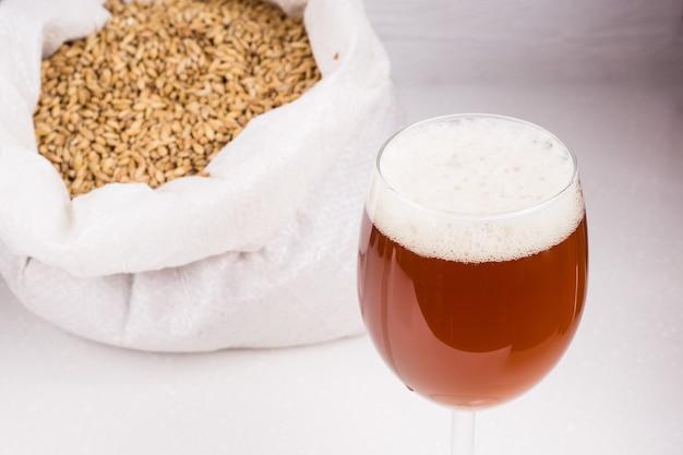 Saco de malte light e copo de cerveja artesanal caseira em uma mesa de madeira com fundo branco