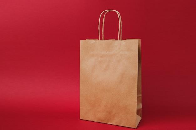 Saco de pacote, saco de papel artesanal em branco claro marrom para take-away isolado em fundo vermelho brilhante. serviço de entrega de produtos alimentícios da loja ou restaurante para o escritório de trabalho. simule o espaço da cópia.