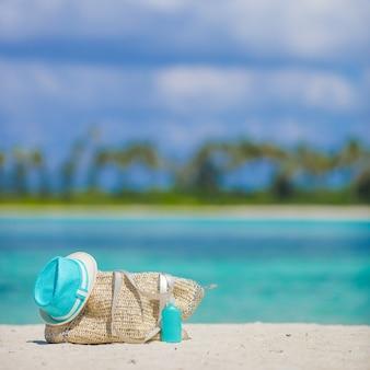 Saco de palha, chapéu azul, óculos escuros e protetor solar garrafa na praia tropical