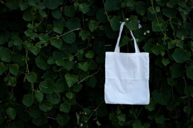 Saco de pano de tecido branco em branco na folhagem de árvores de arbusto verde.