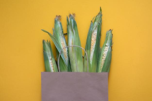 Saco de papel artesanal com colheita de milho em fundo amarelo. vista superior da loja de fazenda de diferentes mantimentos, entrega de comida verde vegana fresca.
