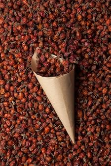 Saco de papel artesanal com rosa mosqueta seca na pilha de frutas secas. bagas saudáveis de crescimento selvagem.