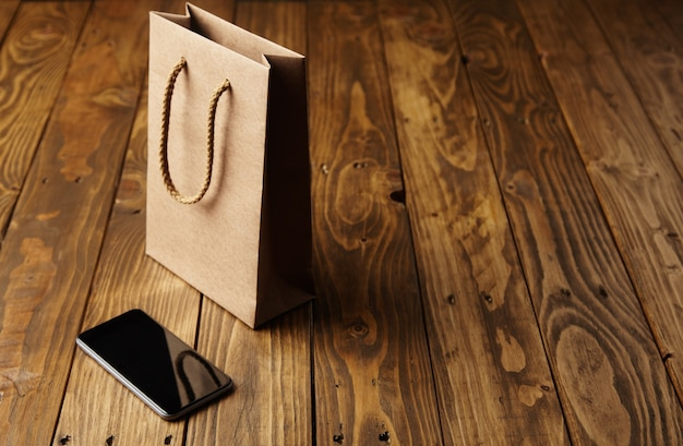 Saco de papel artesanal marrom claro refletido em um smartphone preto imaculado, deitado ao lado dele em uma mesa de madeira feita à mão