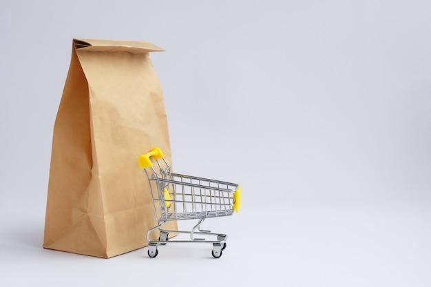 Saco de papel artesanal marrom para compras em um fundo branco e um pequeno carrinho de supermercado