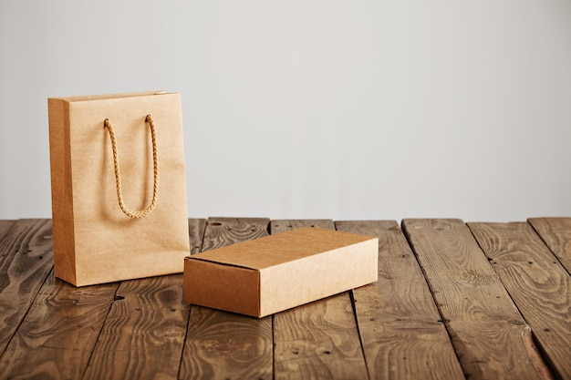 Saco de papel artesanal sem etiqueta ao lado de uma caixa de papelão em branco apresentada em uma mesa de madeira rústica, isolada no fundo branco