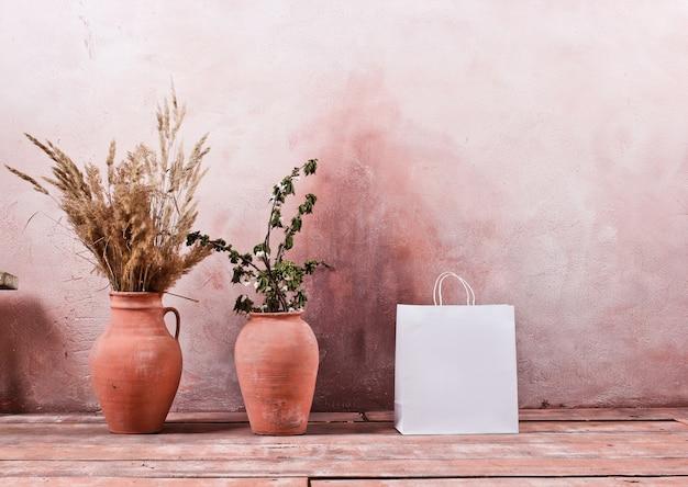 Saco de papel branco sobre a mesa de uma parede com jarros de barro