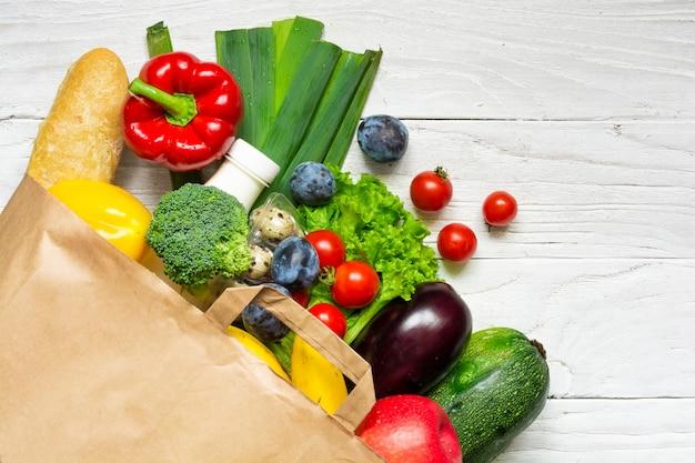 Saco de papel cheio de diferentes alimentos naturais em fundo branco de madeira