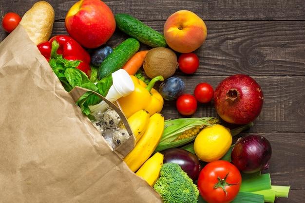 Saco de papel cheio de diferentes alimentos saudáveis em fundo de madeira rústico