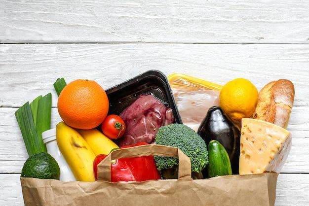 Saco de papel cheio de diferentes alimentos saudáveis na mesa de madeira branca. vista do topo