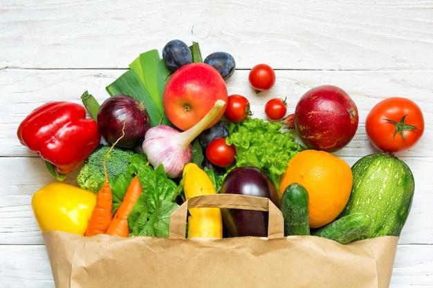 Saco de papel cheio de diferentes frutas e legumes em um fundo branco de madeira