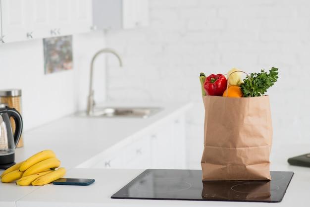 Saco de papel cheio de legumes na cozinha
