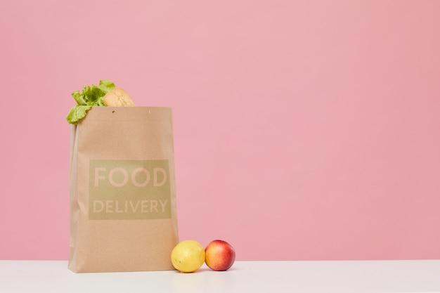 Saco de papel cheio de vegetais e frutas na mesa contra o fundo rosa