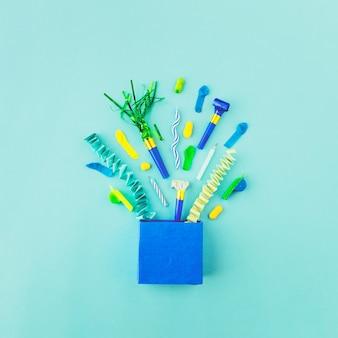 Saco de papel com acessórios de aniversário na superfície verde