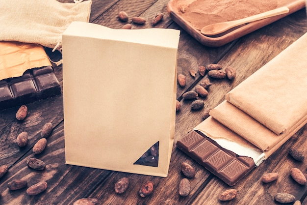 Saco de papel com barras de chocolate e grãos de cacau na mesa de madeira