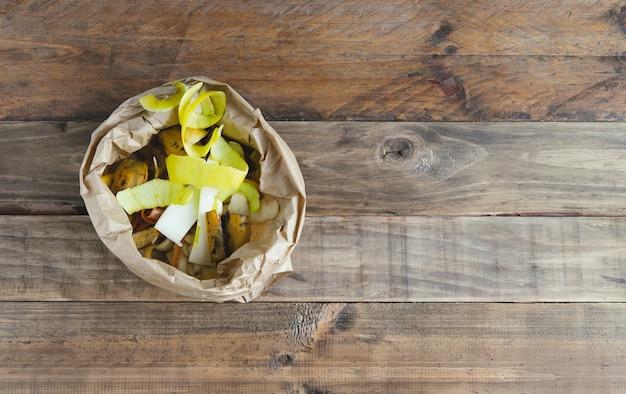 Saco de papel com cascas de frutas com fundo de madeira para compostagem.