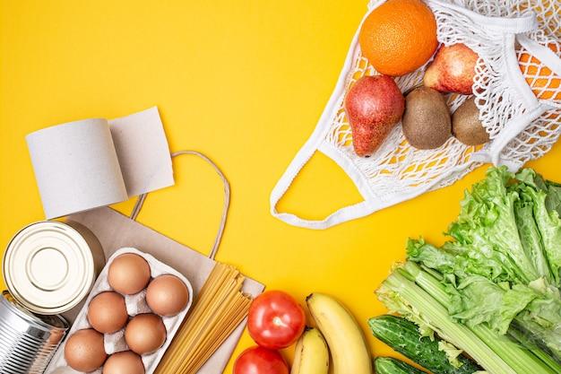 Saco de papel com comida, comida enlatada, tomate, pepino, banana em fundo amarelo.