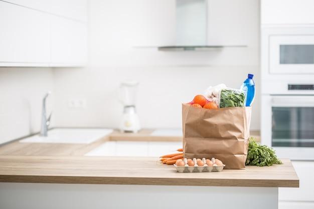 Saco de papel com compra na cozinha de casa.