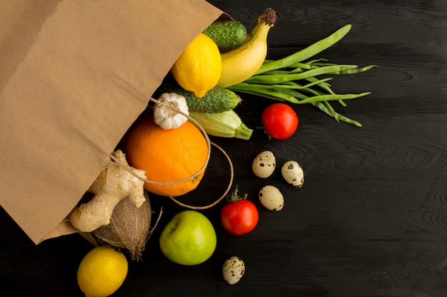 Saco de papel com legumes e frutas na superfície de madeira preta. conceito de comida de saco. vista superior. copie o espaço.