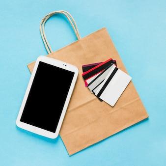 Saco de papel com smartphone e cartões de crédito