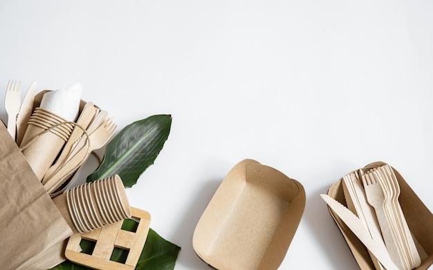 Saco de papel com talheres descartáveis ecológicos, pratos, copos, vista superior.
