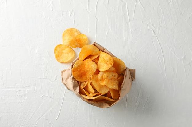 Saco de papel de batatas fritas na madeira branca, espaço para texto. vista do topo