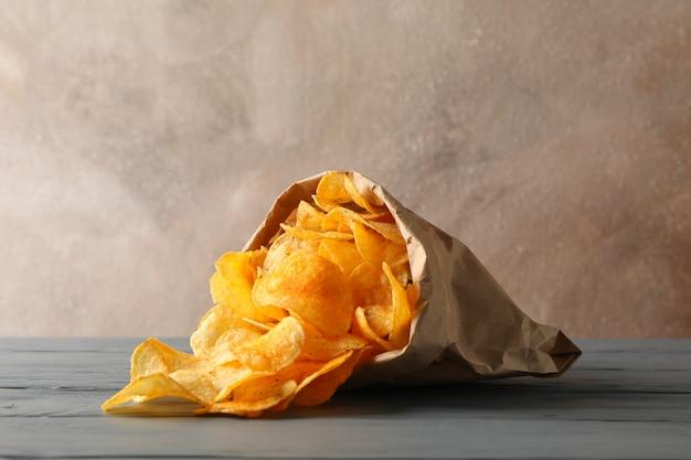 Saco de papel de batatas fritas na madeira cinza, espaço para texto.